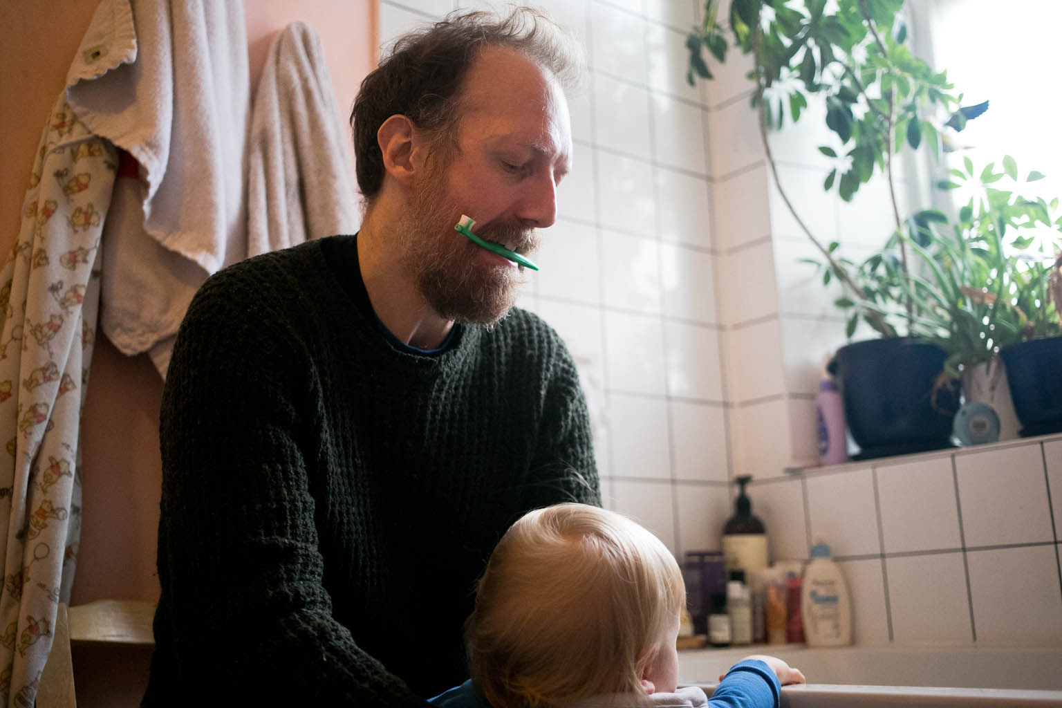 Father with baby toothbrush in teeth picking up son