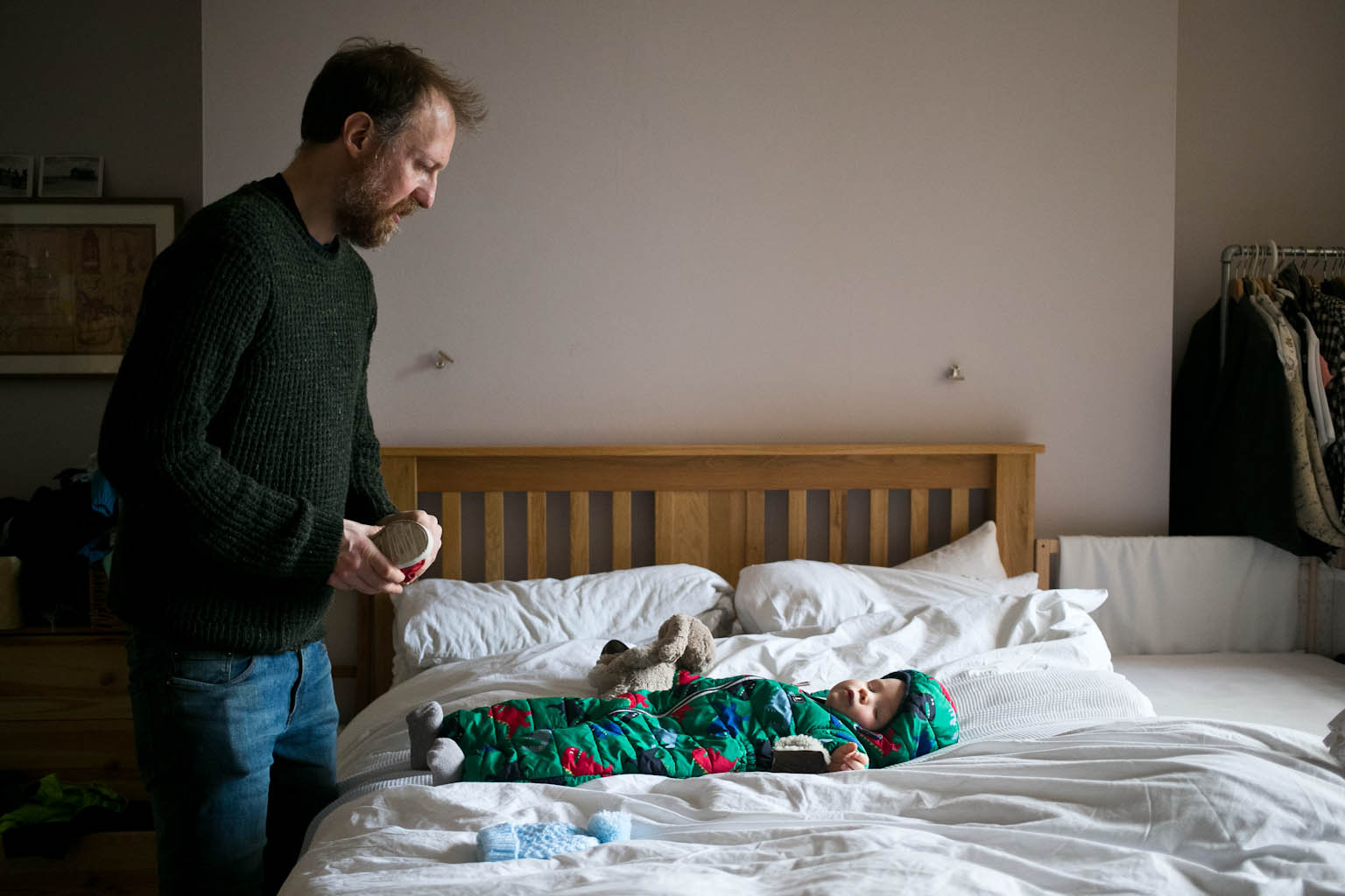 Father holding little shoe looking at sleeping baby boy on bed wearing outdoor suit