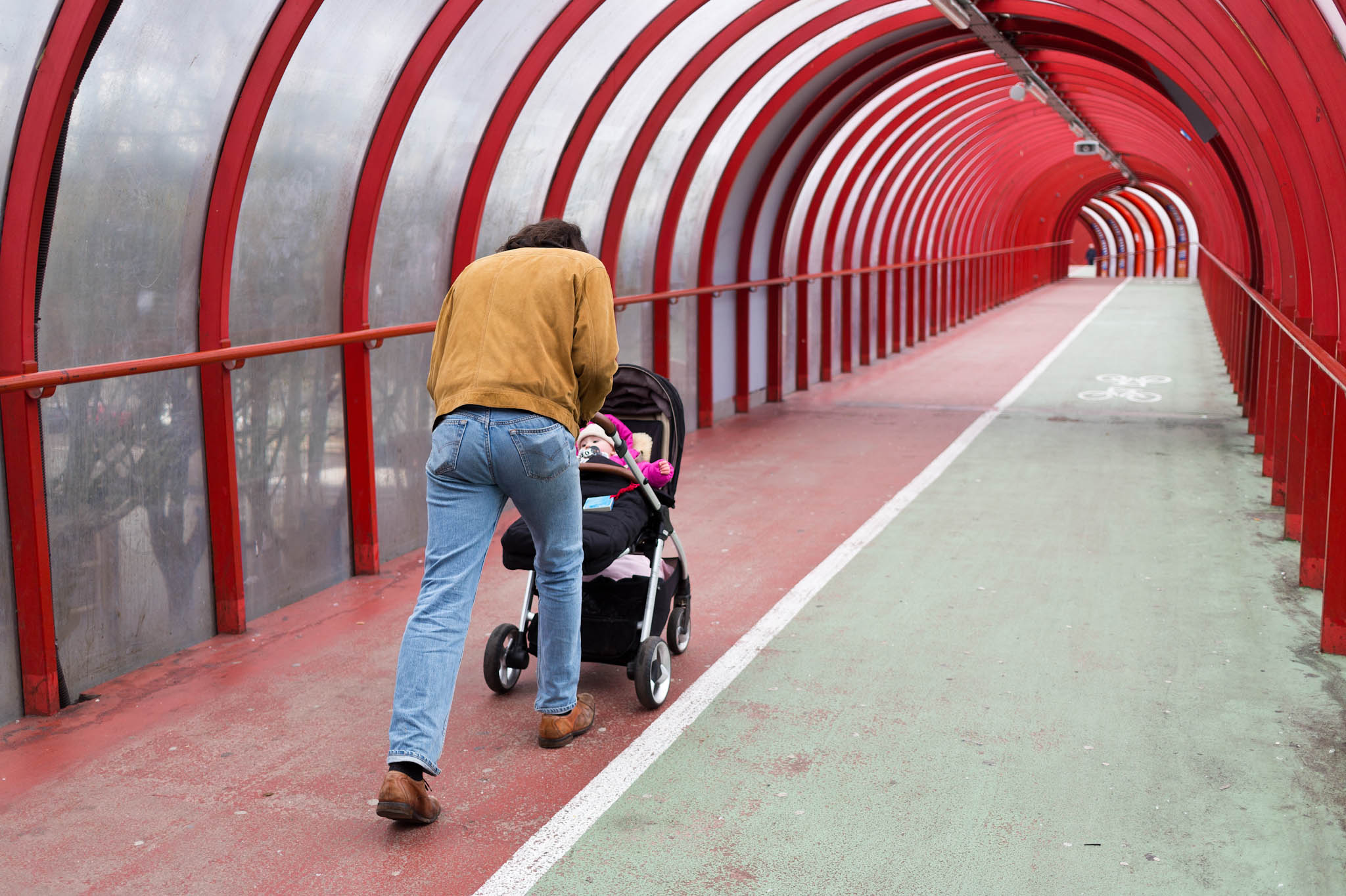 Father pushing pram in tunnel