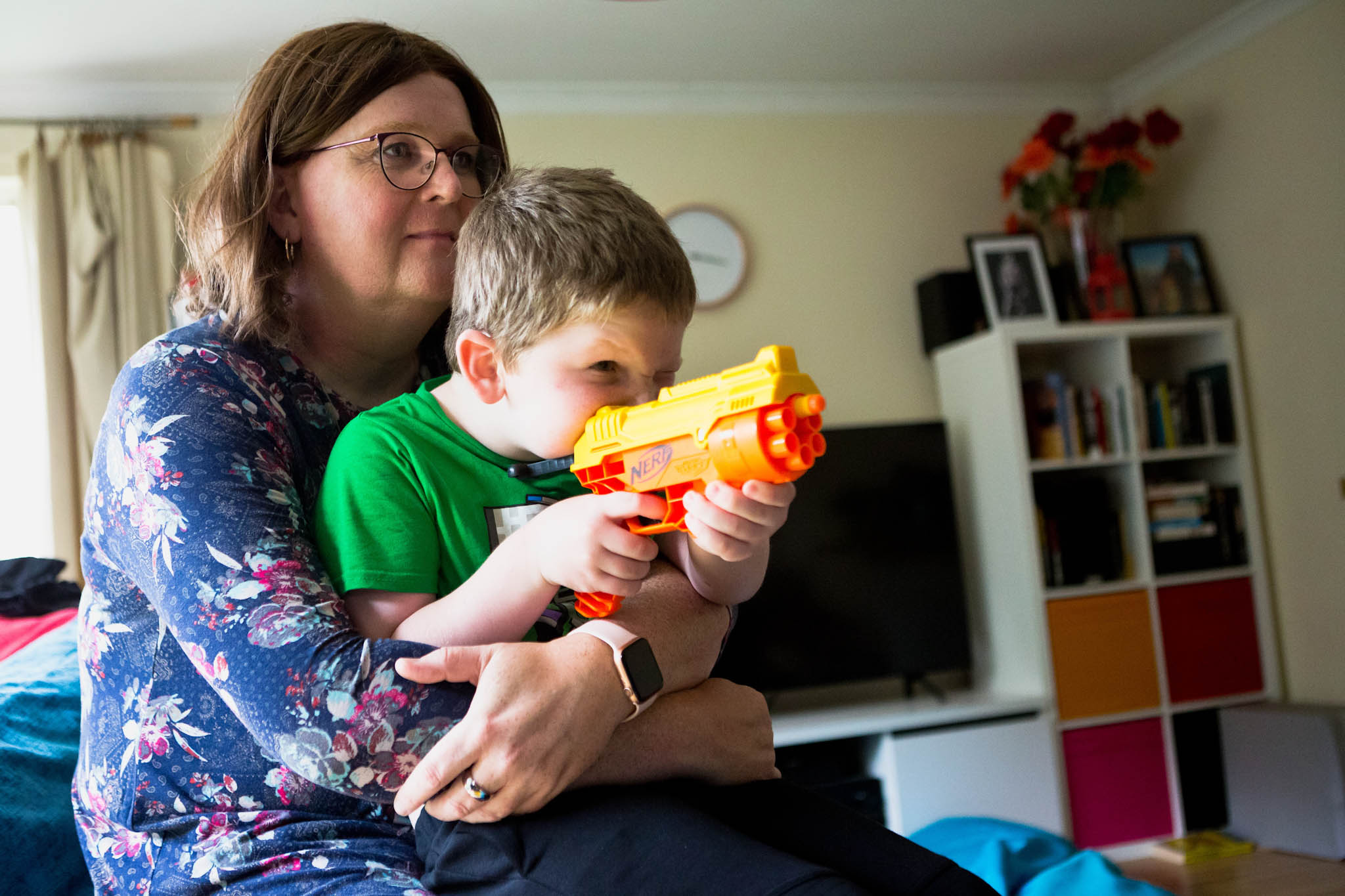 Trans father holding son playing with toy gun