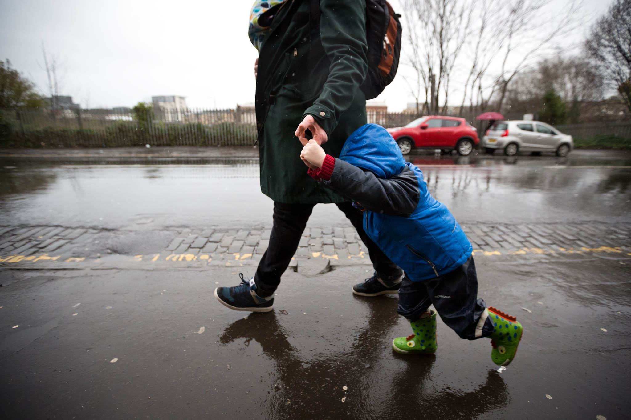Father holding sons hand in rain