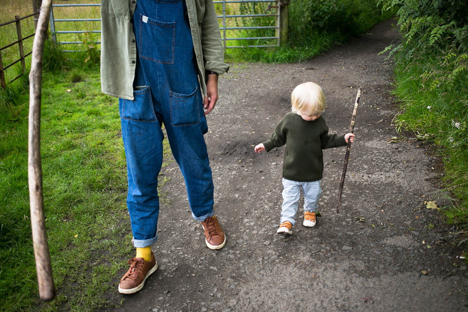 Young boy walking with father both carrying sticks