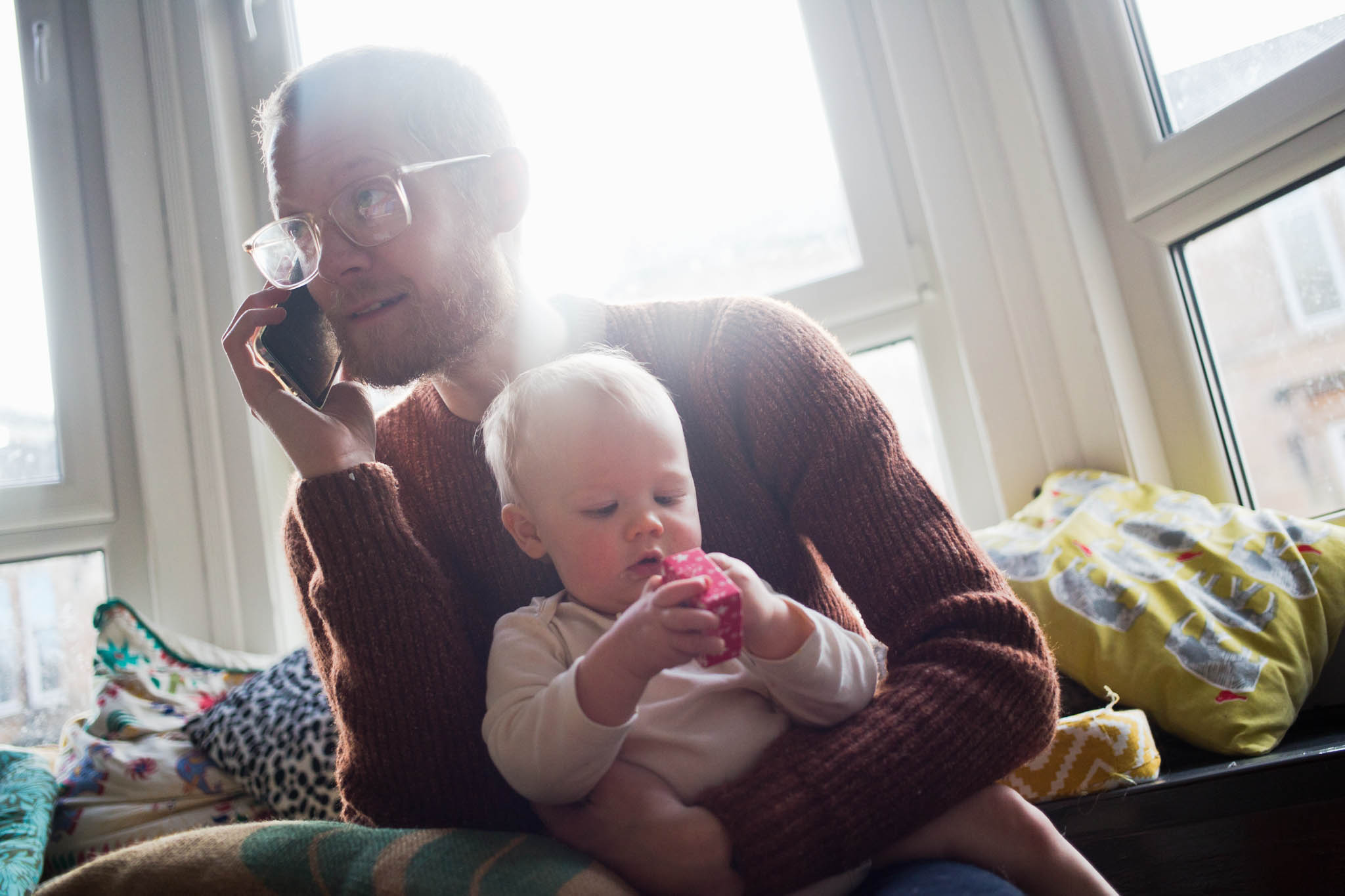 Father on phone holding baby boy