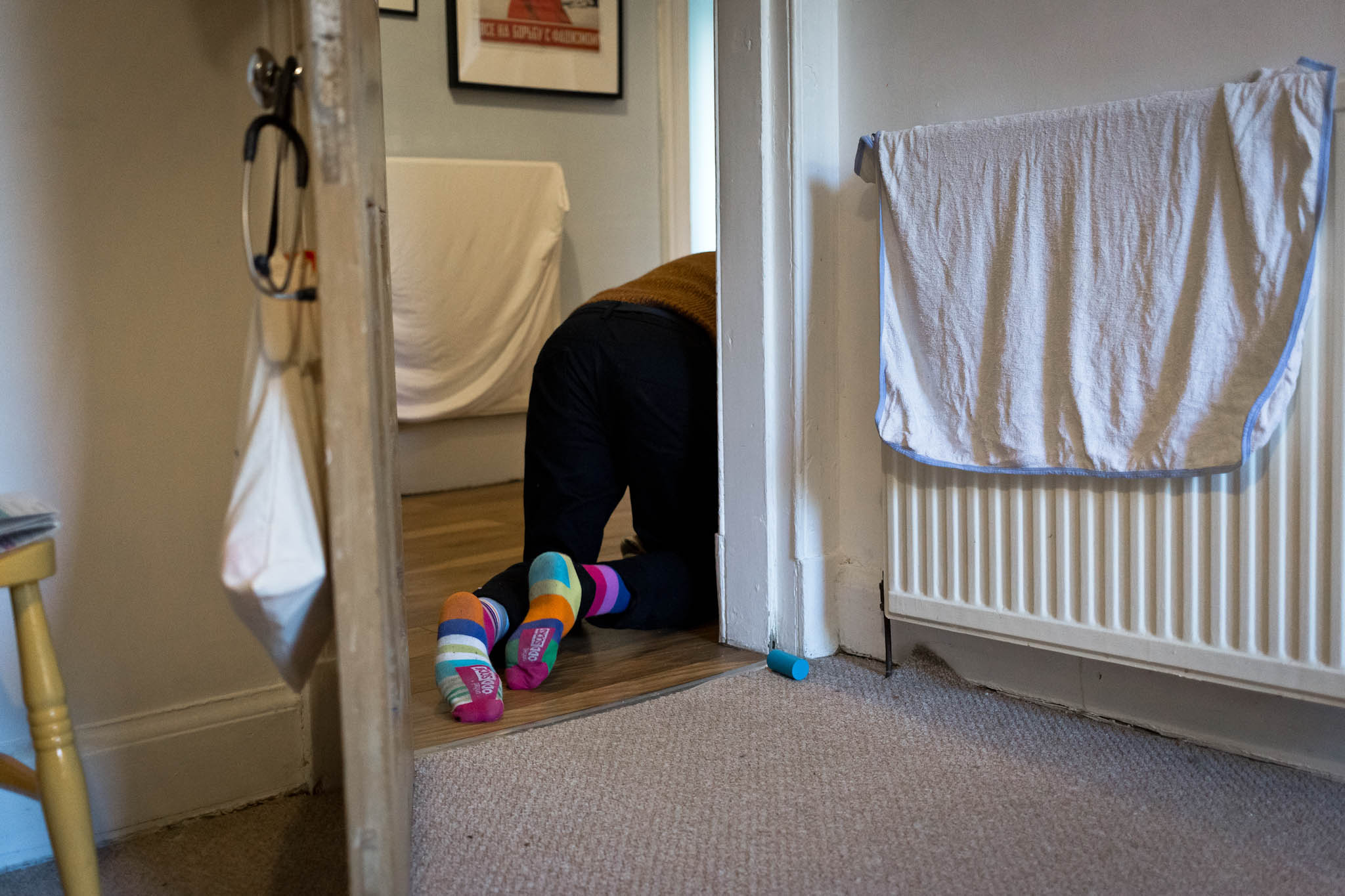 Feet in colourful socks seen crawling away through a doorway following baby