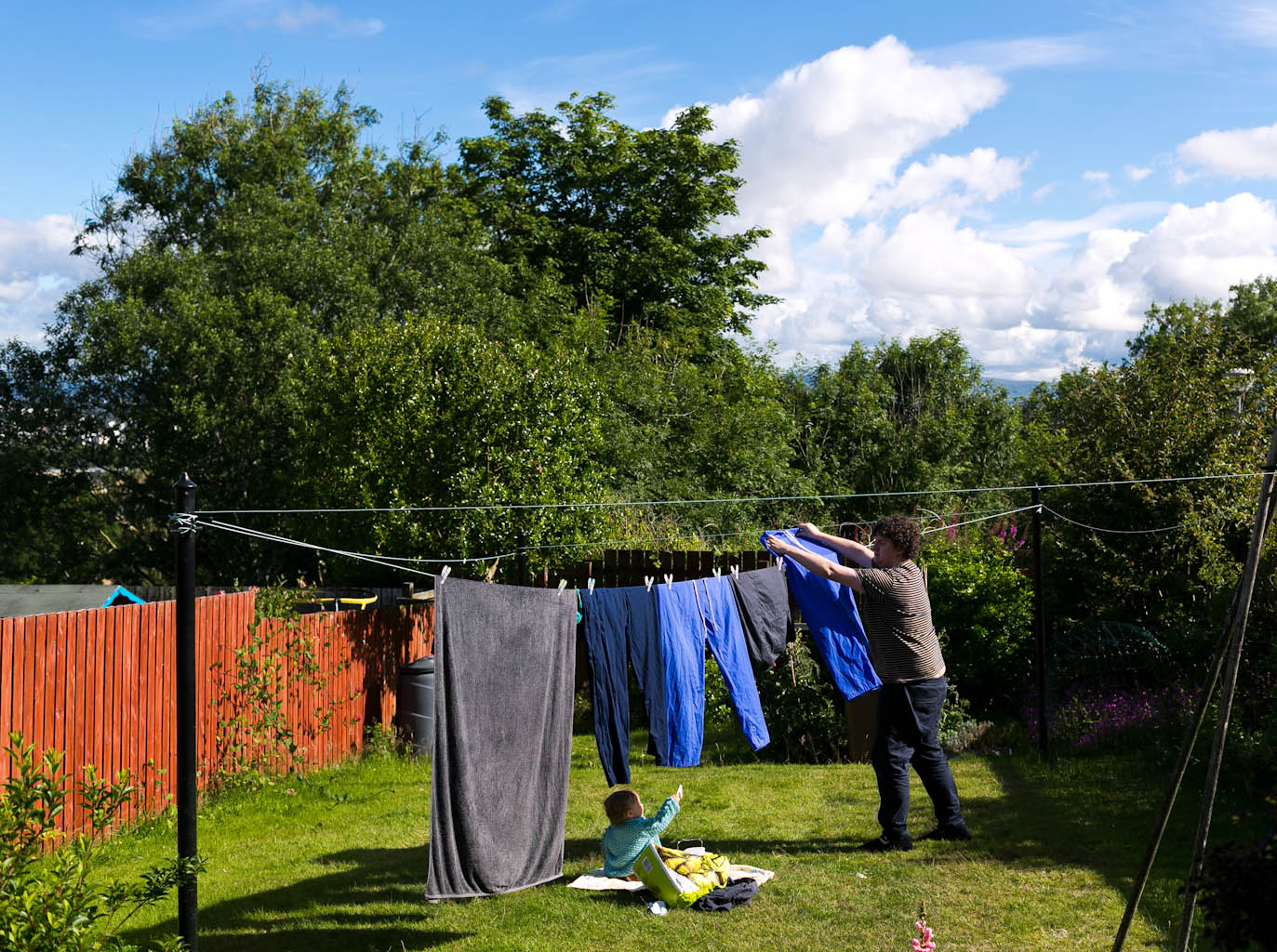 Father hanging washing on line with baby daughter