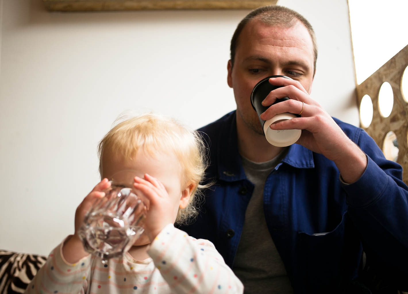 Father drinking takeaway coffee watching young daughter drink a glass of water