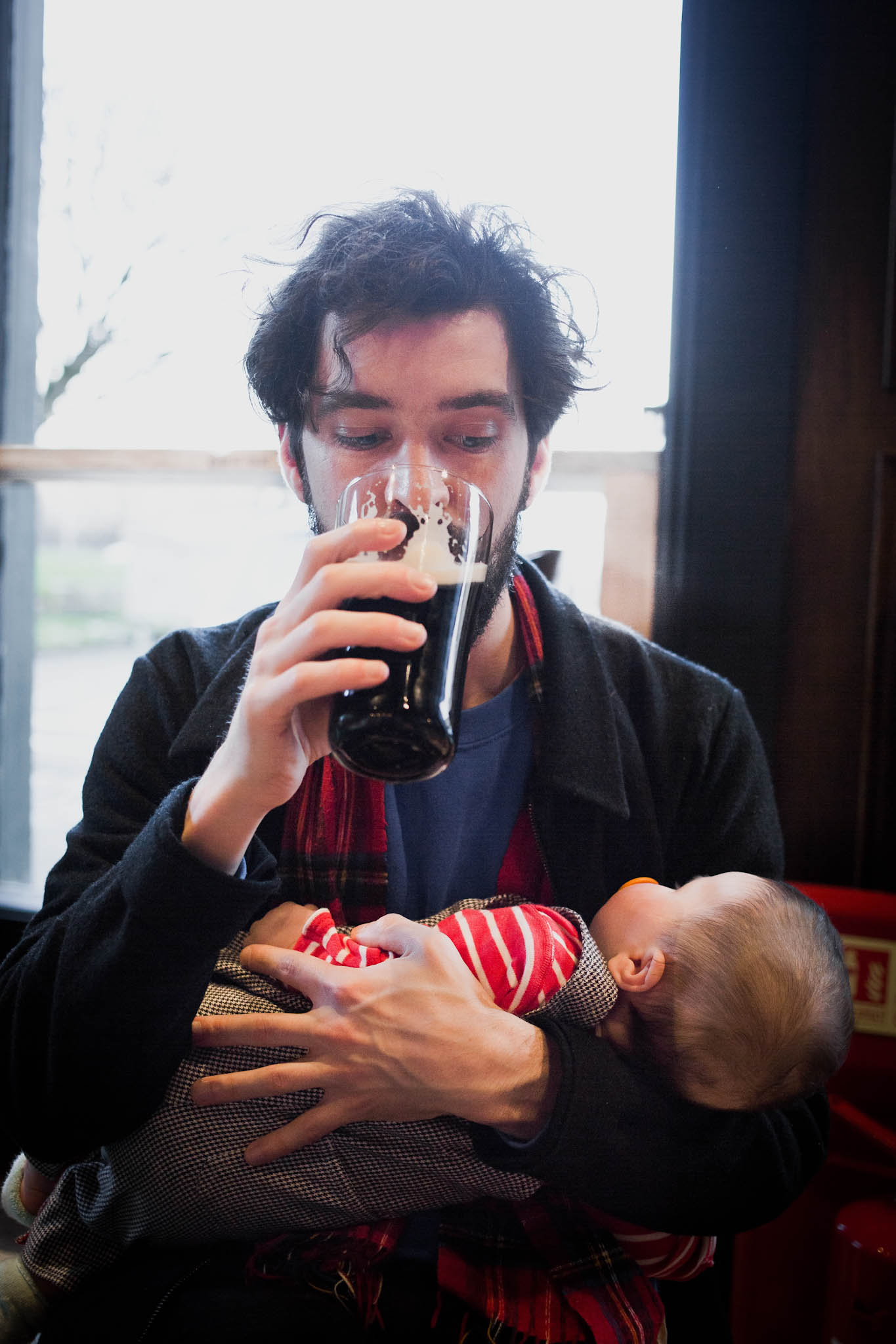 Father drinking pint of guinness watching baby daughter asleep in arms