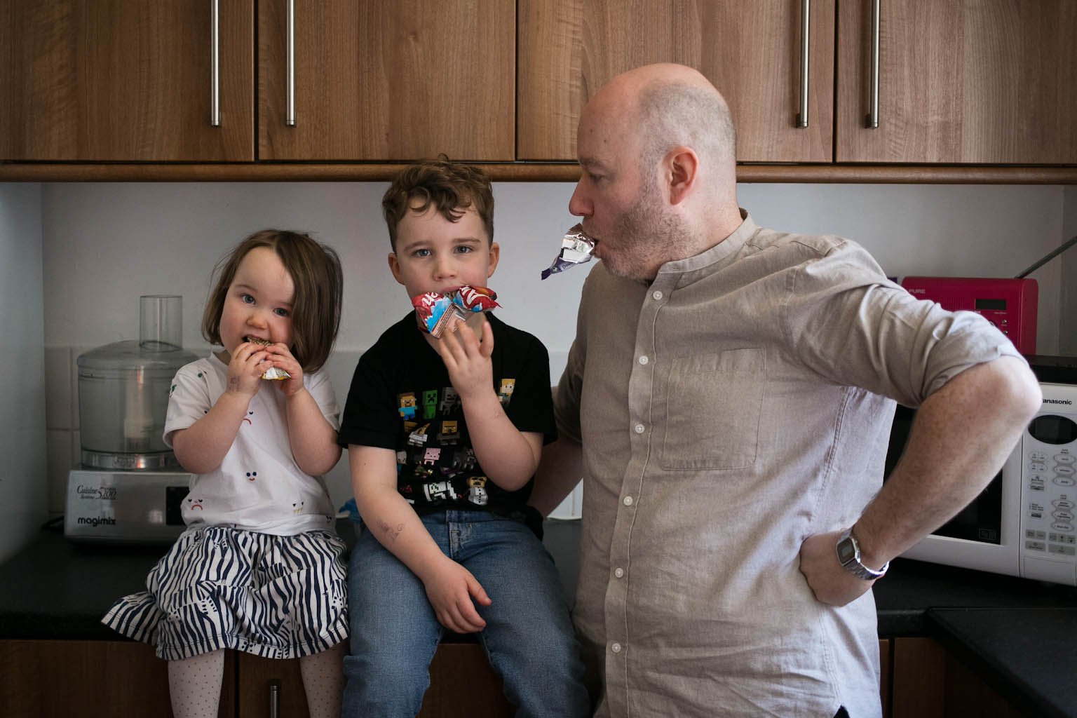Siblings eating snack bars looking to camera while dad jokes with snack bar in mouth