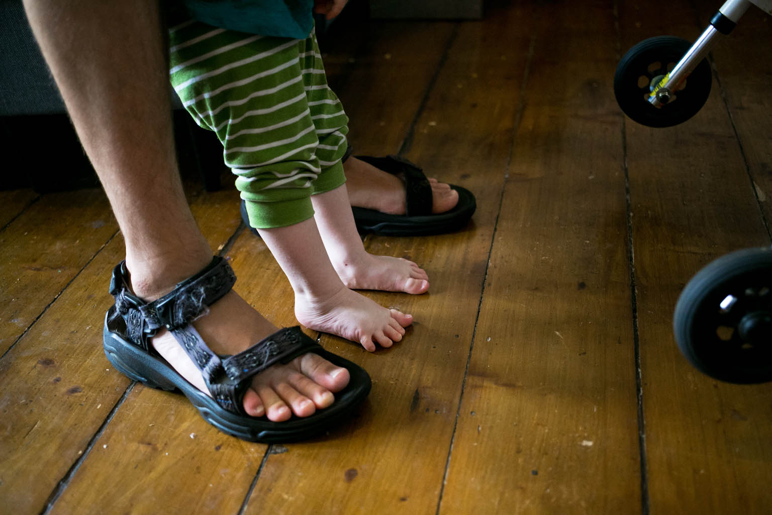 Young boys feet between larger feet in sandles